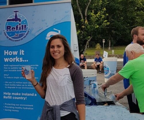 brunette girl holding up Refill.ie branded reusable water cup standing in front of sign at one of Refill.ie's zero waste events