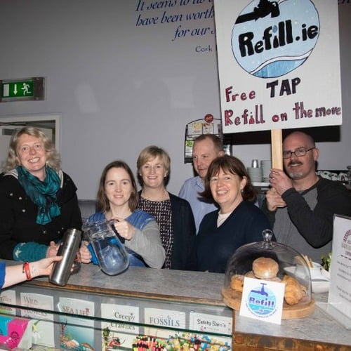 Refill.ie Volunteers standing behind counter with sign