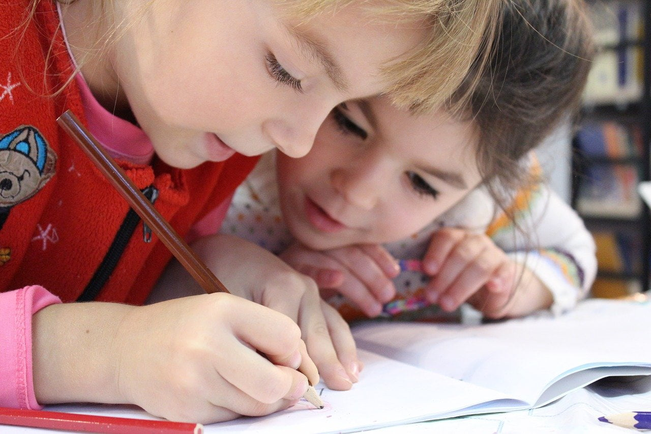 two girls drawing in a notebook with colored pencils